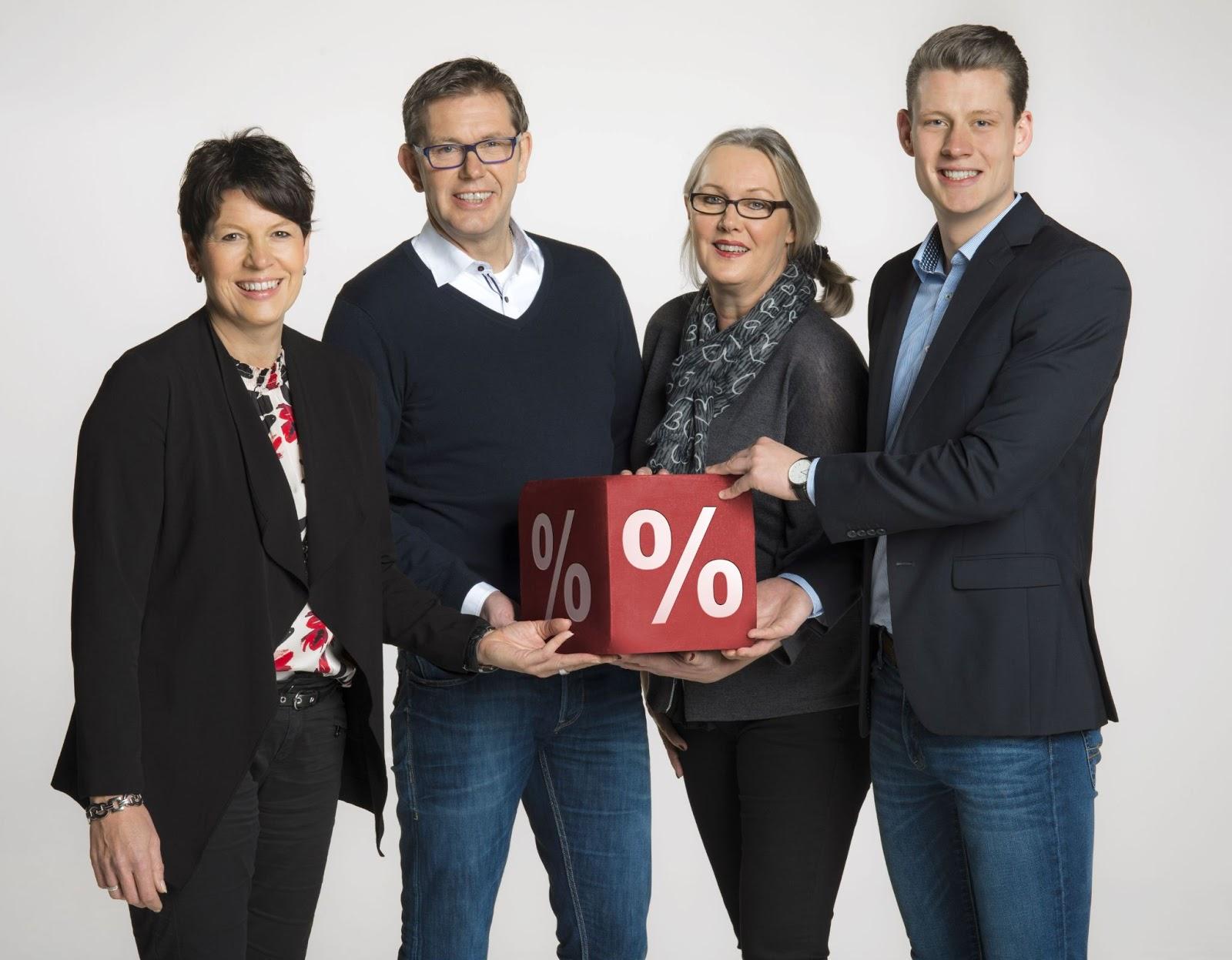Vier Mitarbeiter der Firma halten ein Prozentpaket in den Händen